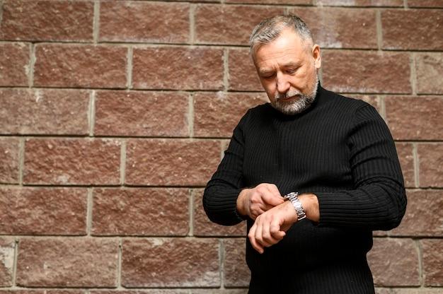 Вид спереди зрелый человек смотрит на часы