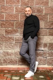 Зрелый мужчина позирует рядом с кирпичной стеной