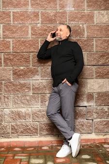 Портрет зрелого человека, стоящего рядом с кирпичной стеной