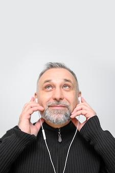 Зрелый человек слушает музыку через наушники