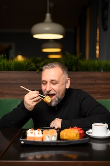 Зрелый человек ест суши
