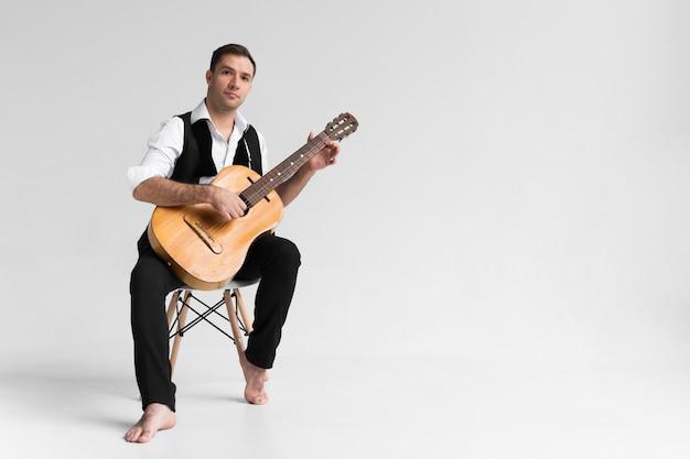 スペースホワイトバックグラウンドとギターを弾く男をコピーします。