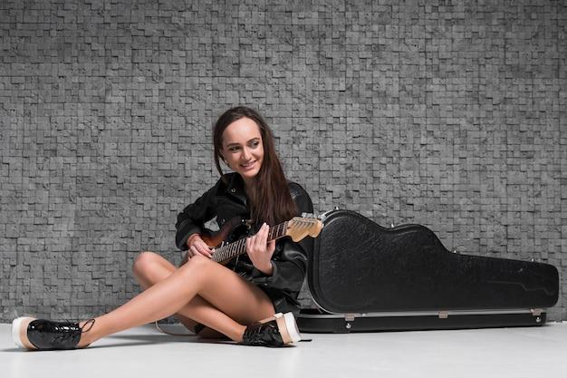 床に座ってギターを弾く女性