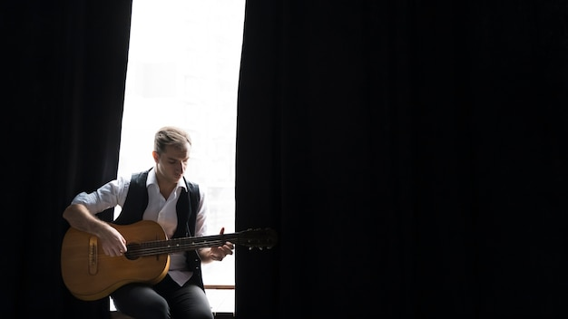 Художник в стиле минимализм с гитарой и черными шторами