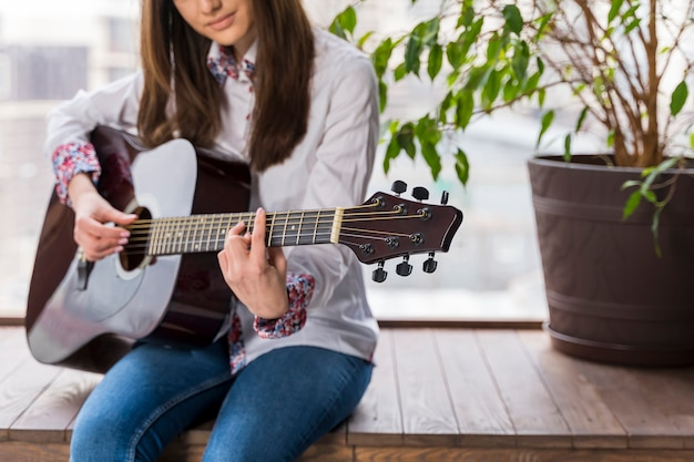 Артист играет на гитаре в помещении и растений
