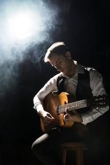 Артист мужчина на сцене играет на классической гитаре