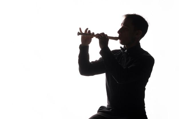 フルートを演奏する男のシルエット