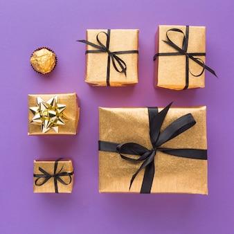 Вид сверху золотых подарков с конфетами