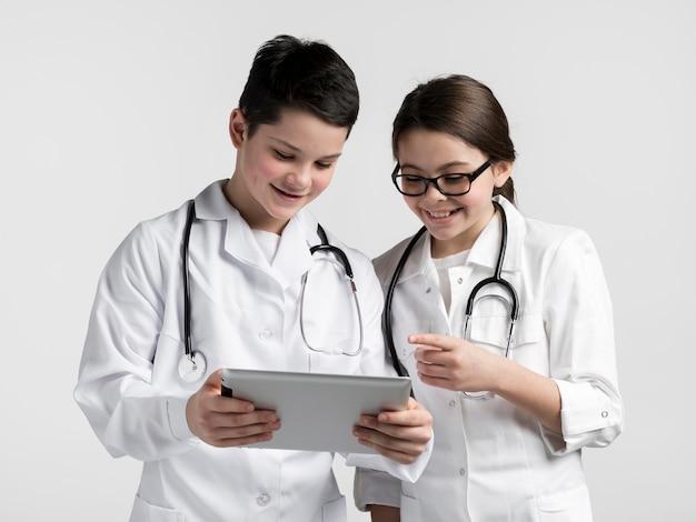 Симпатичные молодые мальчик и девочка вместе с помощью планшета