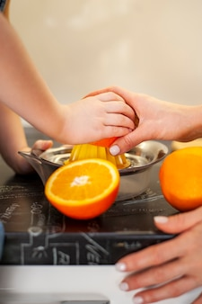 クローズアップ若い女の子とオレンジジュースを準備する母