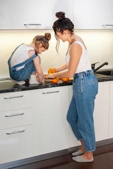 かわいい若い女の子とオレンジジュースを準備する美しい母