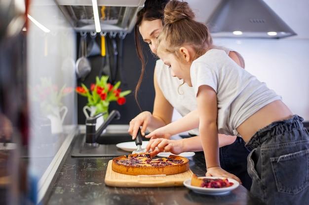 かわいい若い女の子と母親が一緒にケーキを共有