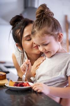 Очаровательная молодая девушка ест вкусный торт