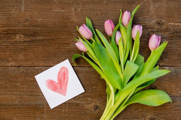 Вид сверху на цветы и рисунок на столе