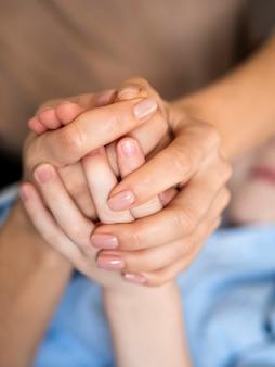 クローズアップの母と手を繋いでいる息子