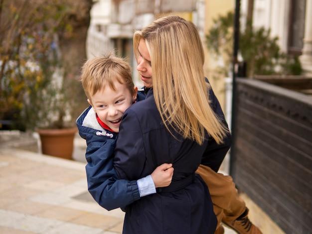 屋外の若い男の子を保持している正面の母