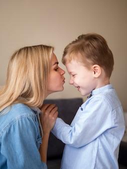 Белокурая мать целует своего милого молодого мальчика