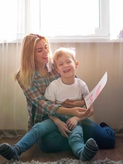 Прелестный мальчик смеясь над детенышами мати