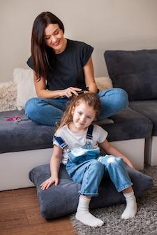 母は彼女のかわいい娘の髪をスタイリング