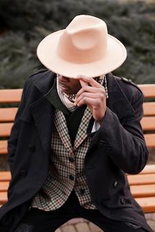 Стильный взрослый мужчина в шляпе позирует на улице