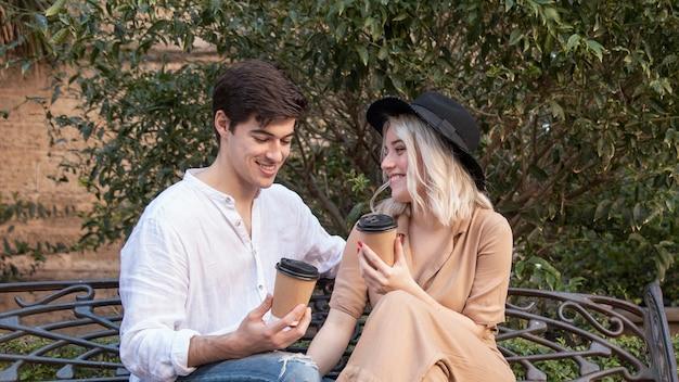 Счастливая пара, наслаждаясь кофе на скамейке