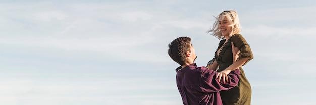 Взгляд со стороны человека поднимая женщину вверх с космосом экземпляра