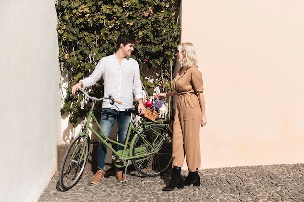 Пара с велосипедом, наслаждаясь прогулкой