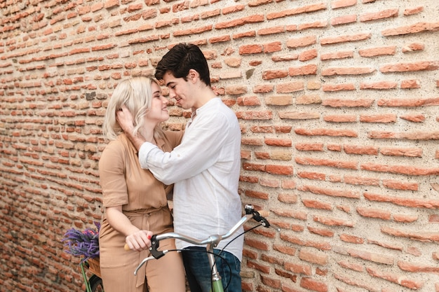 Пара склоняется к поцелую с велосипедом и копией пространства