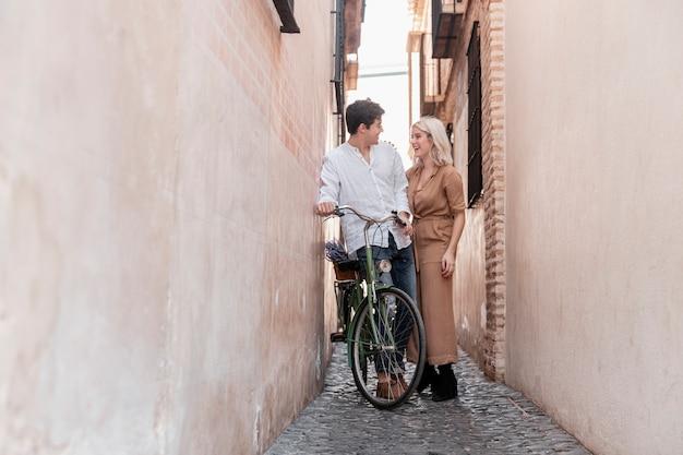 Пара с велосипедом на открытом воздухе
