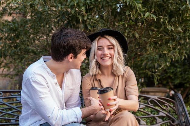 Улыбающаяся пара наслаждается кофе на скамейке