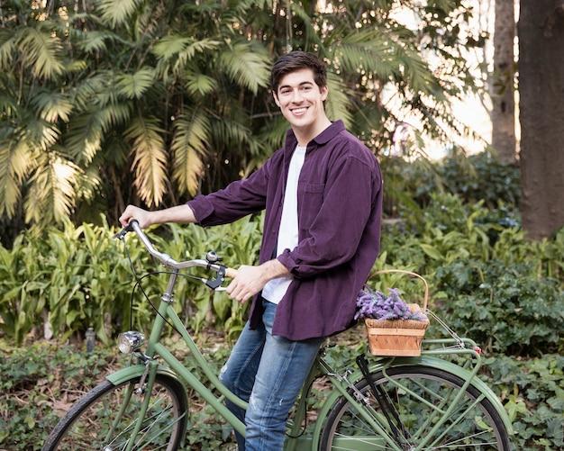 Вид сбоку человека на велосипеде в парке