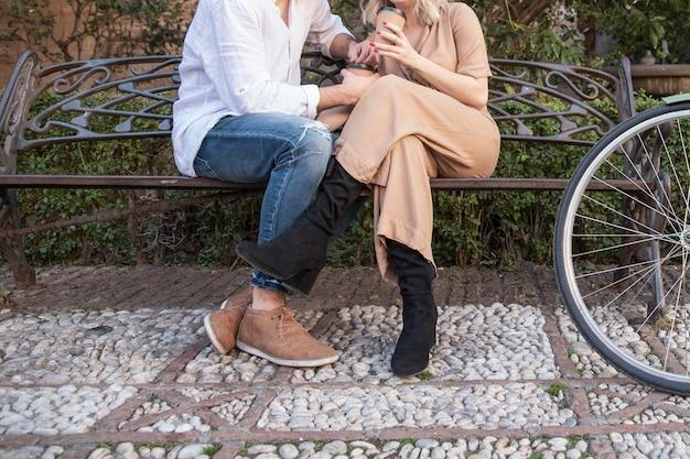 Мужчина и женщина на скамейке с велосипедом