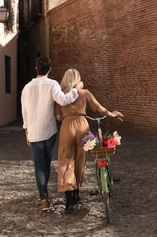 Вид сзади пара гуляет с велосипедом