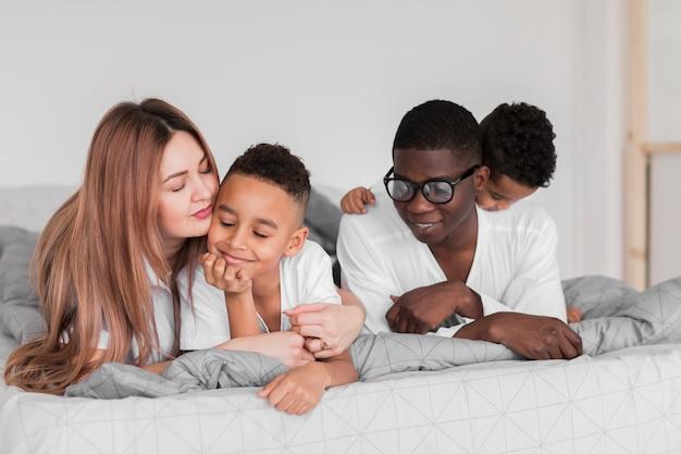 幸せな多文化家族のベッドに滞在