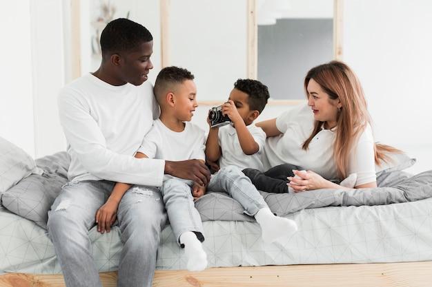 Многокультурная семья играет с камерой в помещении