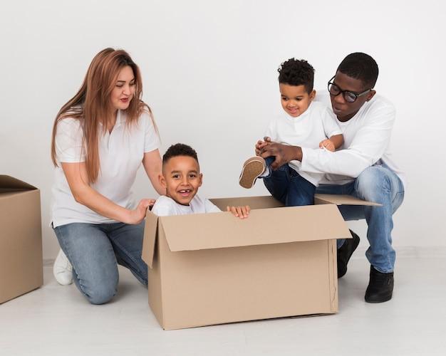 Родители и дети играют с коробкой
