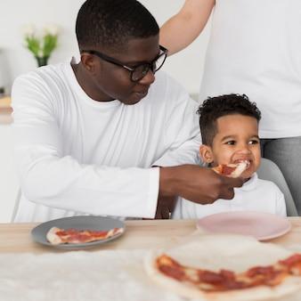 父と子がピザを食べる