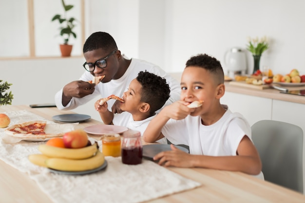 Отец ест пиццу с сыновьями