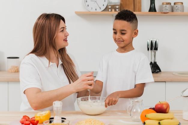 Мать учит сына готовить еду на кухне