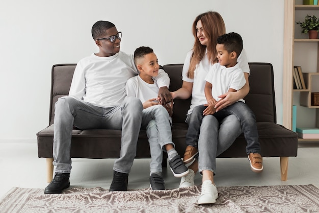 Многокультурная семья, проводящая время вместе на диване