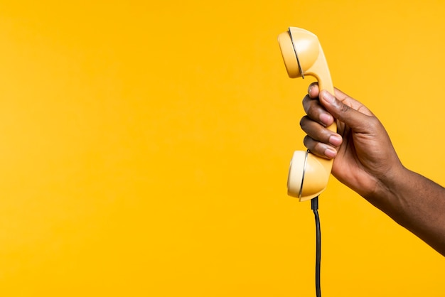 古い携帯電話を保持しているコピースペース男
