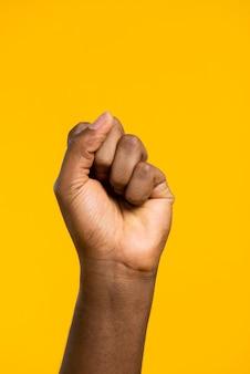 Кулак вид спереди на желтом фоне