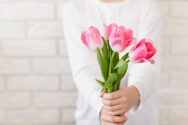 花を保持しているクローズアップ少年