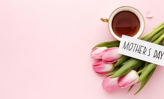 Вид сверху чашка с чаем возле тюльпанов