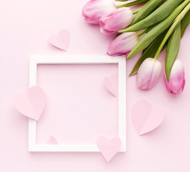 フレームの横にあるテーブルの上のチューリップの花束