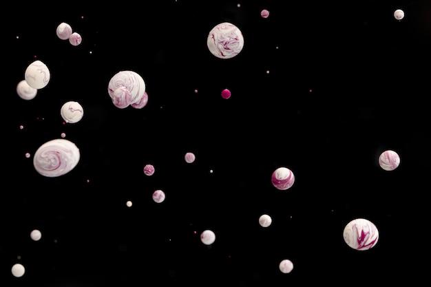 黒の背景に水で抽象的な白いアクリルボール