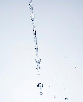 白い背景の上の現実的な水のしぶき