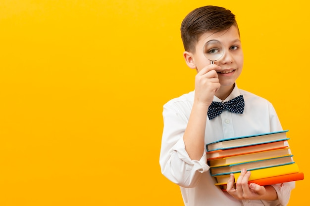 書籍のスタックを保持している少年