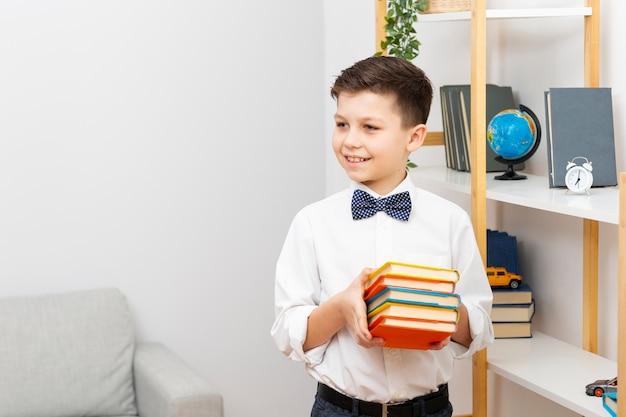 書籍のスタックを保持しているスマイリーの小さな男の子