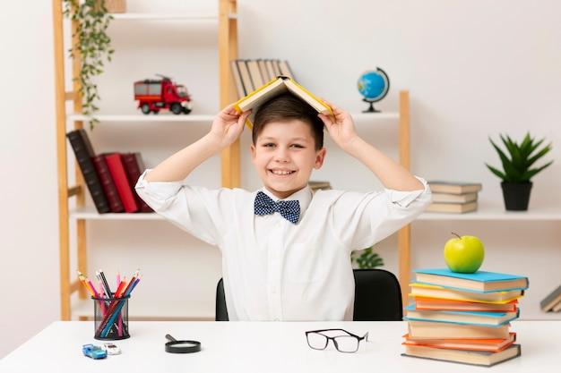 本で遊ぶ遊び心のある少年